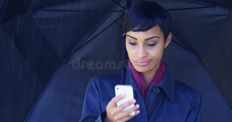 Vrouw in regenonweer wordt geplakt die telefoongesprek proberen te maken dat royalty-vrije stock afbeeldingen