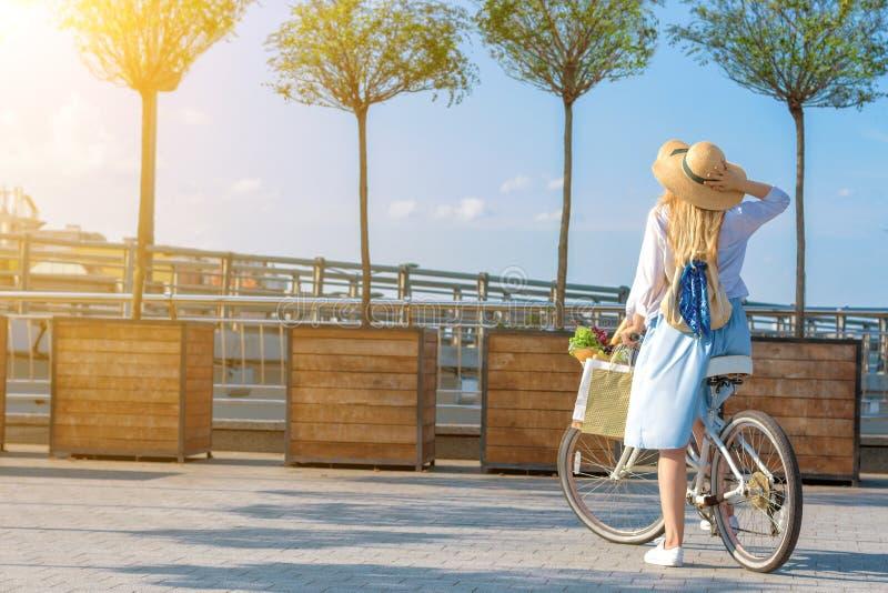 Vrouw in retro blauwe kleding die witte fiets berijden op zonsondergang royalty-vrije stock afbeeldingen