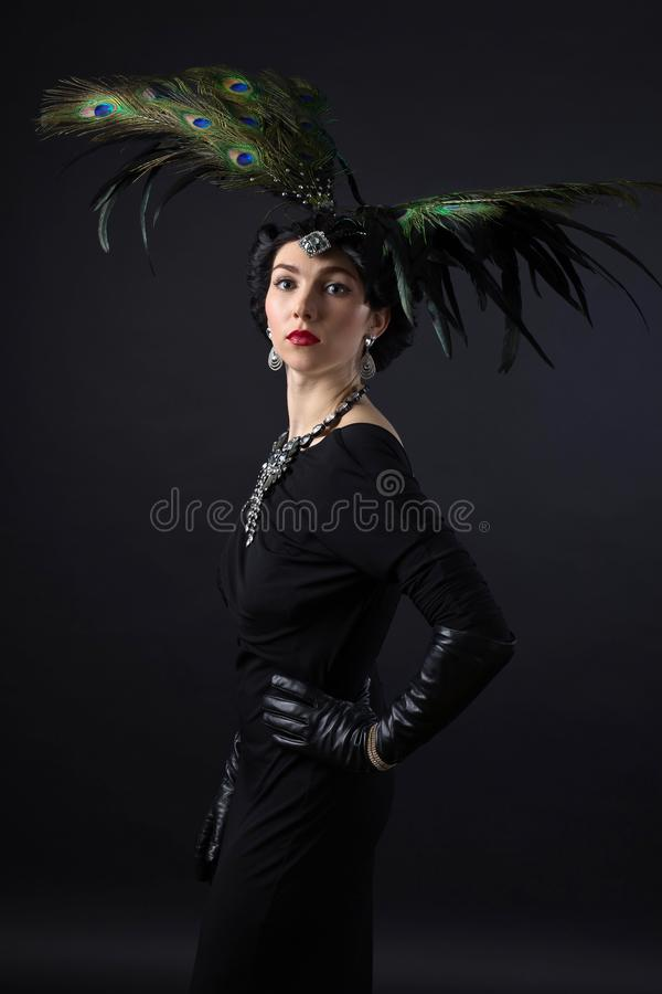 Vrouw in retro stijl met veerhoofddeksel stock afbeeldingen