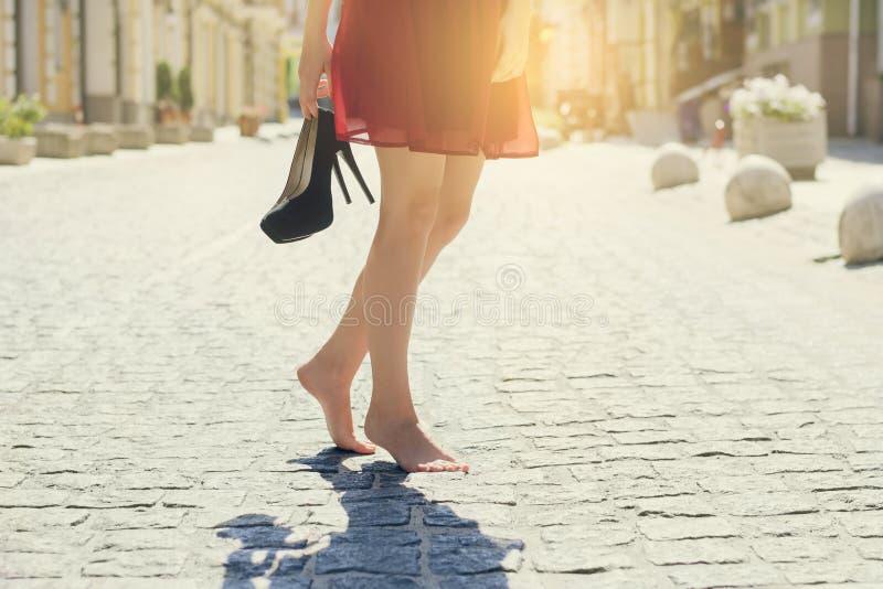Vrouw in rode elegante kleding, die hoge hielschoenen in hand houden en stock afbeeldingen