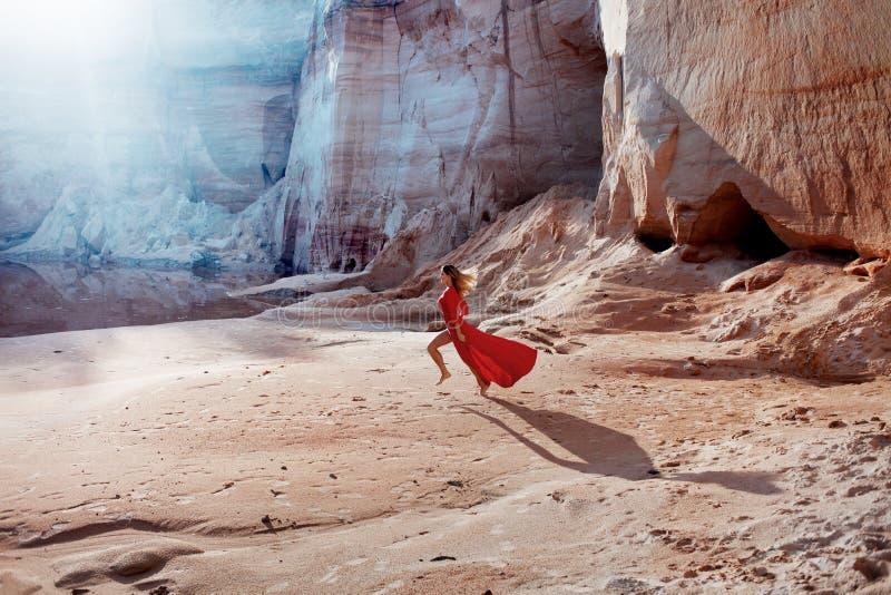 Vrouw in rode golvende kleding met het vliegen stoffenlooppas stock afbeelding