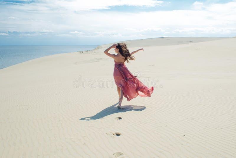 Vrouw in rode golvende kleding met het vliegen stoffenlooppas op achtergrond van duinen royalty-vrije stock afbeelding