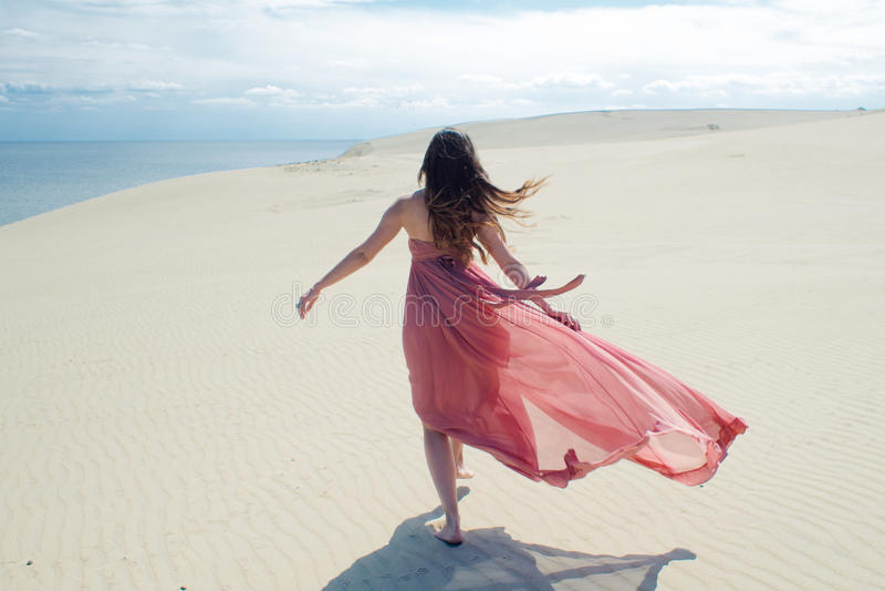 Vrouw in rode golvende kleding met het vliegen stoffenlooppas op achtergrond van duinen Achter mening stock foto