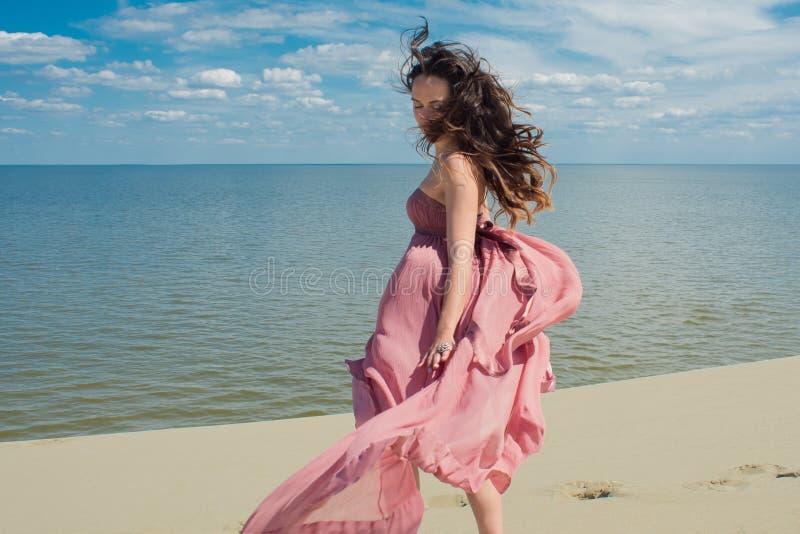 Vrouw in rode golvende kleding met het vliegen stoffenlooppas op achtergrond van duinen Horizon en het overzees royalty-vrije stock foto