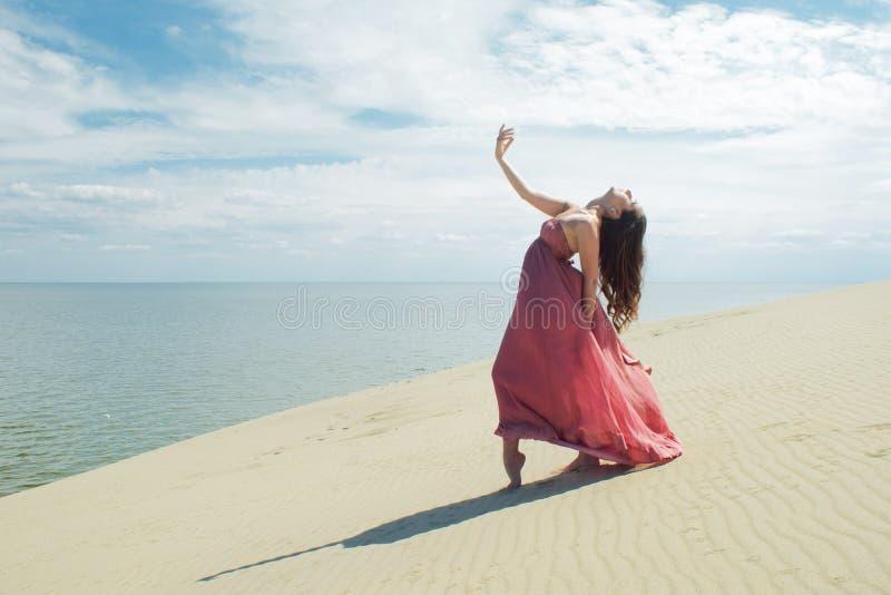 Vrouw in rode golvende kleding met het vliegen stoffenlooppas op achtergrond van duinen Turner op de rug van het duin royalty-vrije stock afbeeldingen