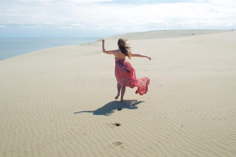 Vrouw in rode golvende kleding met het vliegen stoffenlooppas ver weg, achtermening stock afbeelding