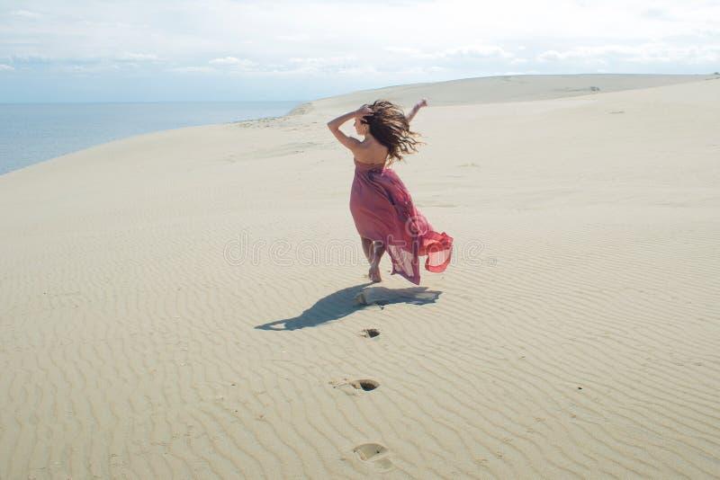 Vrouw in rode golvende kleding met het vliegen stoffenlooppas ver weg, achtermening stock foto's