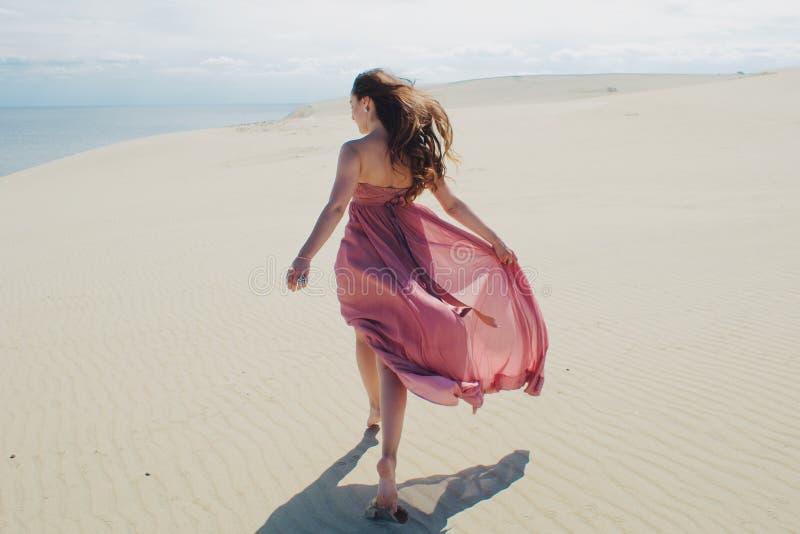 Vrouw in rode golvende kleding met het vliegen stoffenlooppas ver weg, achtermening stock foto