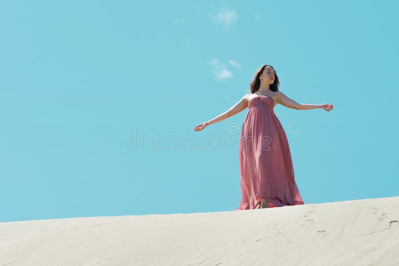 Vrouw in rode golvende kleding met vliegende stof, het Mooie meisje spinnen stock afbeeldingen