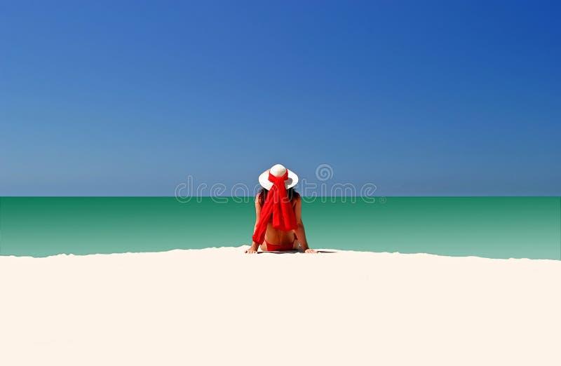 Vrouw in Rode hoed en bikini die al alleen op leeg strand zit stock foto's