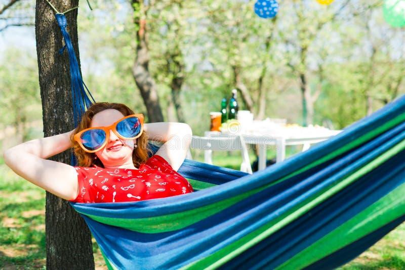 Vrouw in rode kleding en grote grappige zonglazen die op hangmat liggen stock afbeeldingen