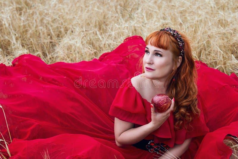 Vrouw in rode kleding met een appel in zijn handzitting op een gerst royalty-vrije stock fotografie