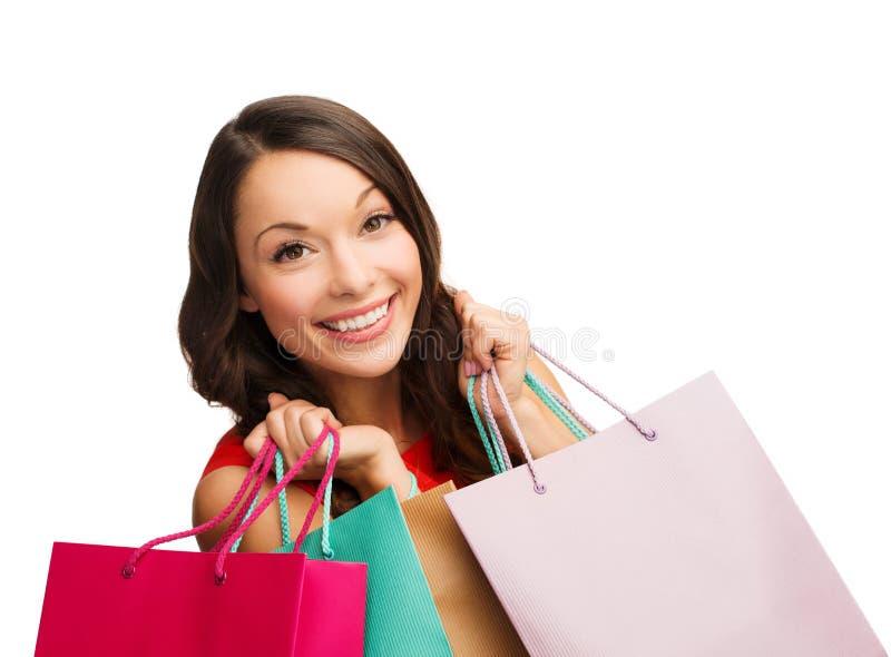 Vrouw in rode kleding met het winkelen zakken stock foto