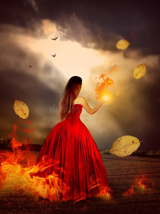 Vrouw in rode kleding met magische brand stock afbeelding