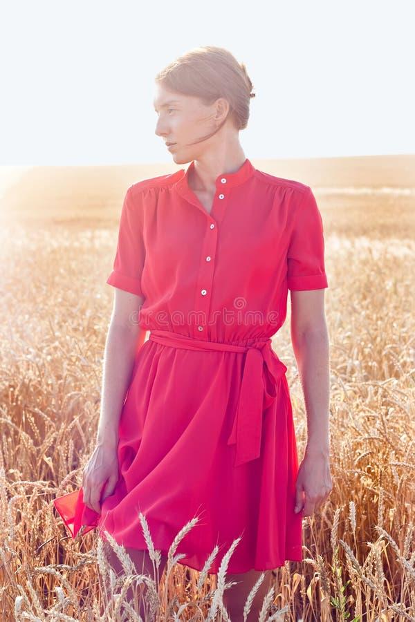 Vrouw in rode kleding op geel tarwegebied royalty-vrije stock foto