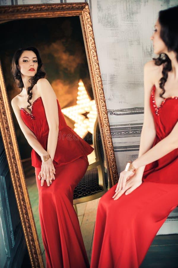 Vrouw in rode kleding vóór spiegel stock foto's