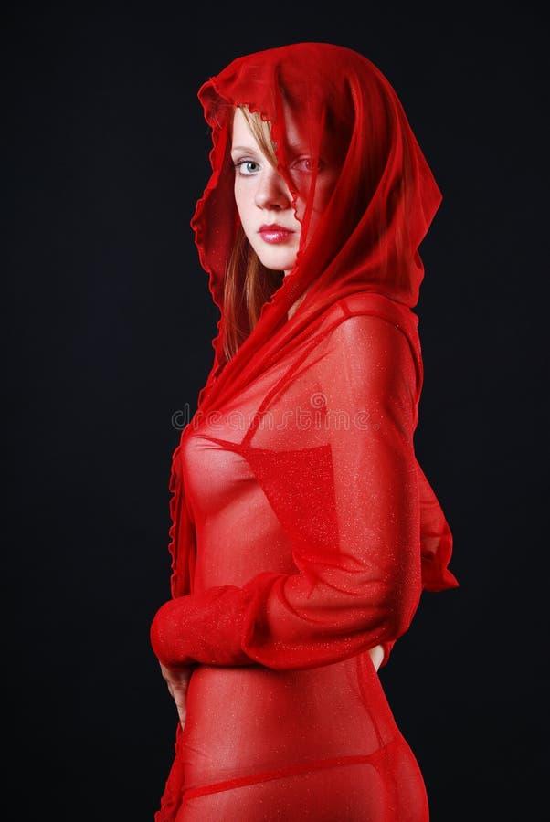 Vrouw in rode transparant met kap stock afbeelding