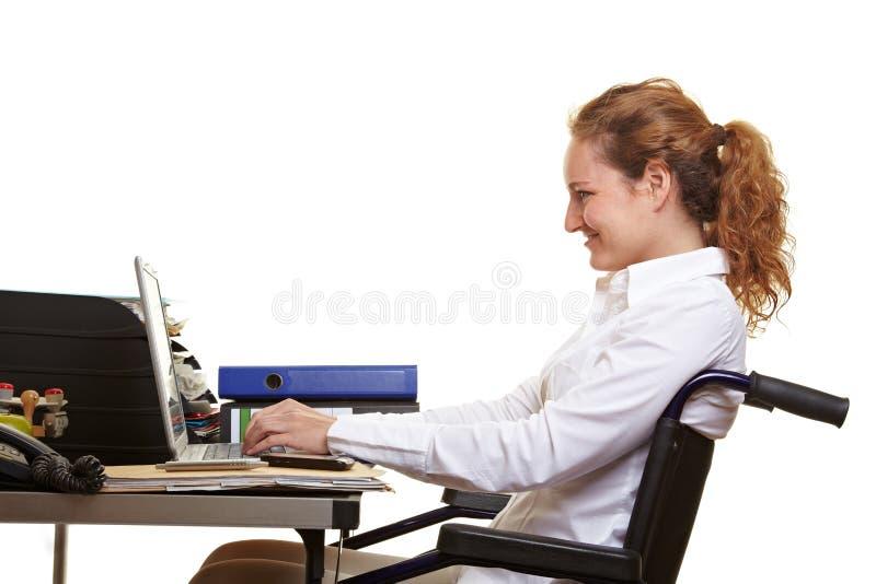 Vrouw in rolstoel die bij bureau werkt stock fotografie