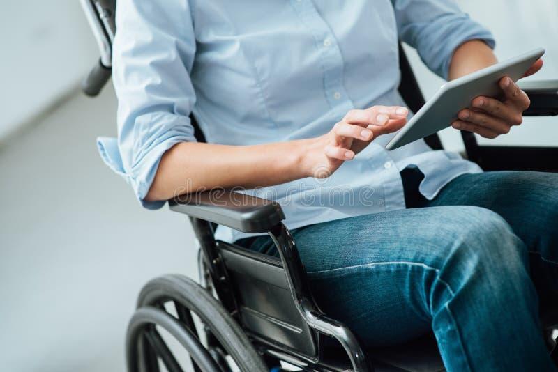 Vrouw in rolstoel die een tablet gebruiken stock afbeelding