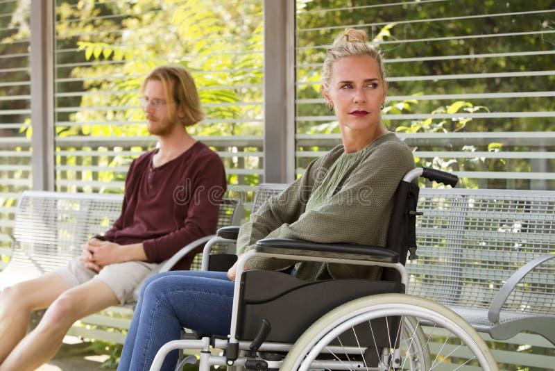 Vrouw in rolstoel naast de jonge mens op bank royalty-vrije stock afbeeldingen