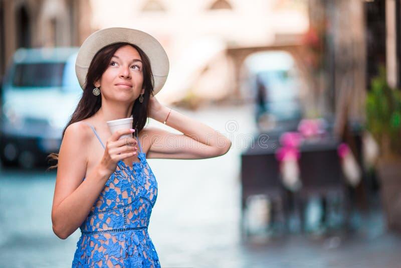 Vrouw in Rome met koffie om op vakantiereis te gaan Glimlachend gelukkig Kaukasisch meisje die pret hebben die op Italiaanse stoe royalty-vrije stock afbeelding