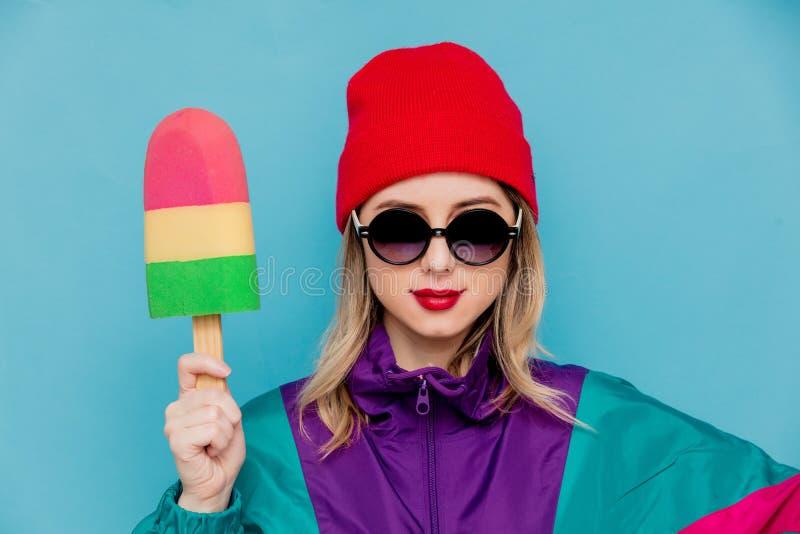 Vrouw in rood hoed, zonnebril en kostuum van jaren '90 met stuk speelgoed roomijs stock afbeeldingen
