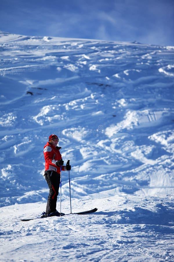 Vrouw in rood op skihelling royalty-vrije stock afbeelding