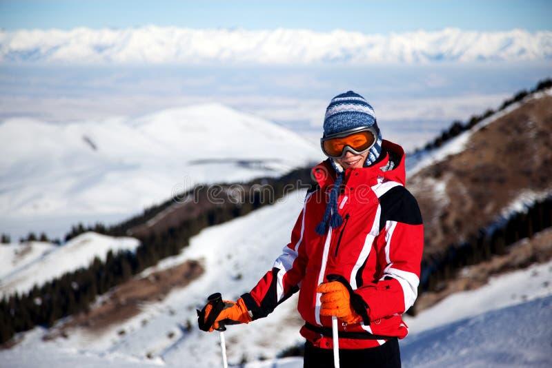 Vrouw in rood op skihelling stock afbeelding