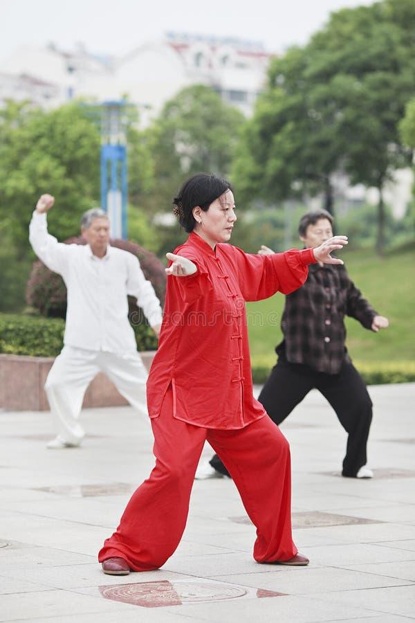 Vrouw in rood praktizerend Tai Chi, Yangzhou, China stock foto's