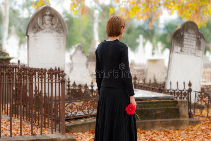 Vrouw in Rouwen die in Begraafplaats lopen stock foto