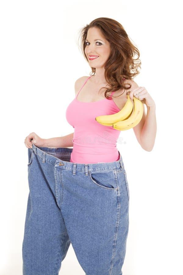 Vrouw in roze bovenkant met bananen grote broek stock afbeelding