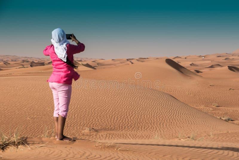 Vrouw in Roze die Beeld in Emirati-Woestijn die van Sharjah nemen Ghutia dragen stock fotografie