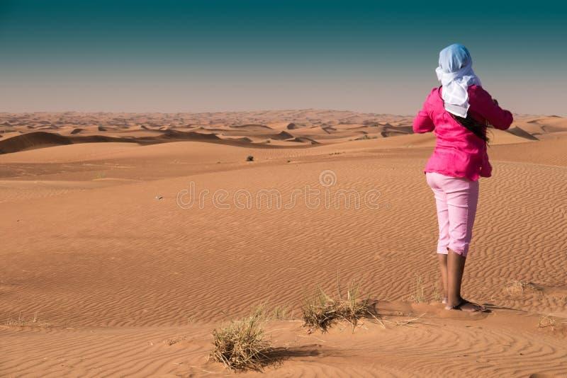 Vrouw in Roze die Beeld in Emirati-Woestijn die van Sharjah nemen Ghutia dragen stock afbeelding