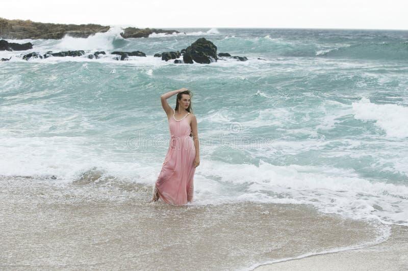 Vrouw in roze kleding die zich in verpletterende golven van oceaan bevinden royalty-vrije stock afbeeldingen