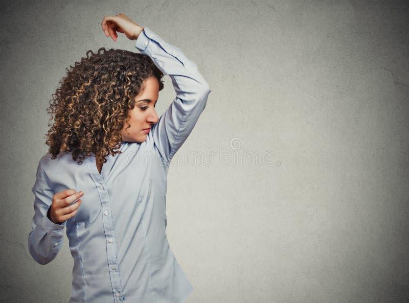 Vrouw ruiken die haar oksel snuiven iets stinkt royalty-vrije stock foto's