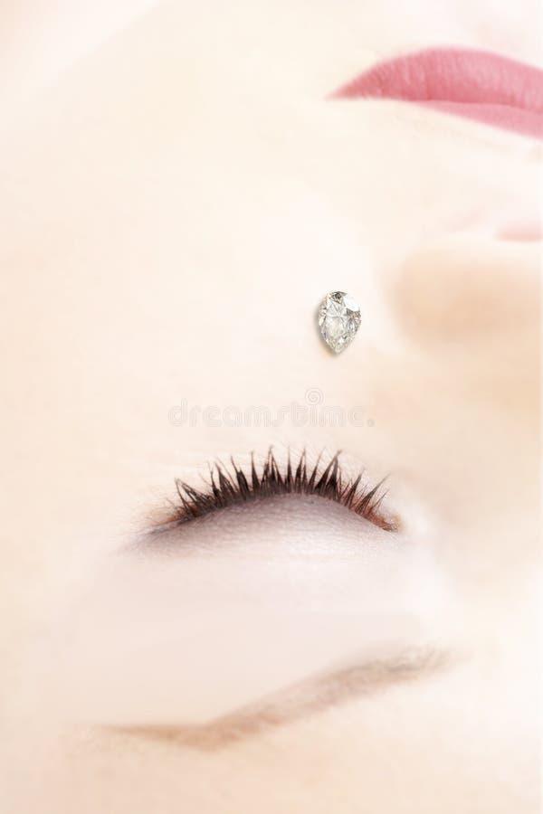 Vrouw? s gezicht met een diamant stock foto's