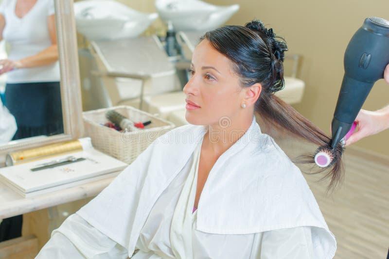 Vrouw in salon die haar gedaan krijgen stock fotografie