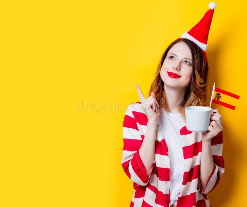 Vrouw in Santa Claus-hoed met de vlag en de kop van Spanje stock fotografie