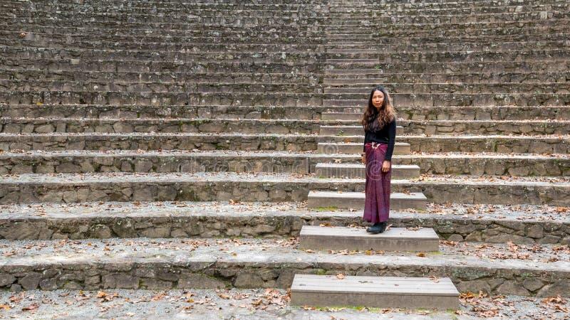 Vrouw in sarongen in amfitheater die zich op stappen bevinden die kijken naar royalty-vrije stock foto