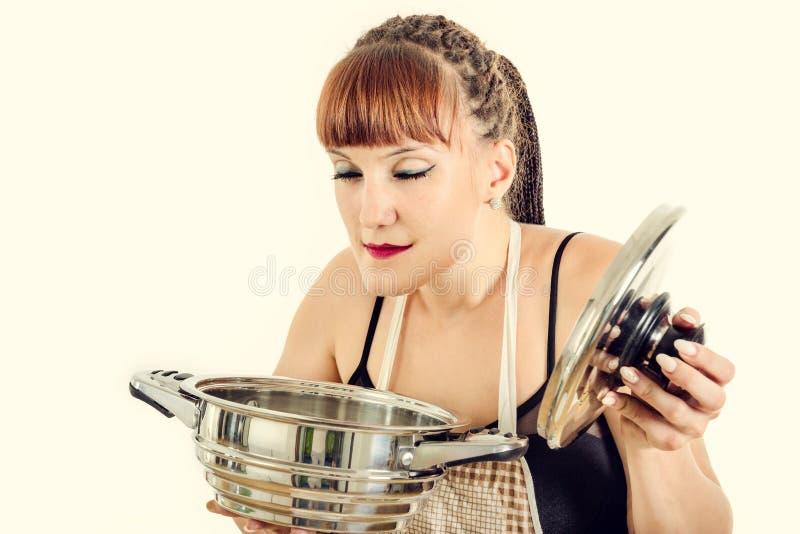 Vrouw in schort ruikend voedsel van de pot royalty-vrije stock afbeelding