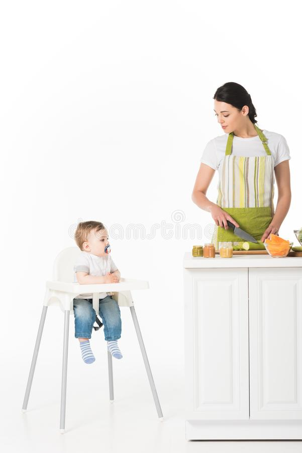 vrouw in schort scherpe courgette en het bekijken weinig zoon met de zitting van de babyfopspeen stock foto's
