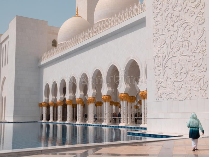 Vrouw in Sheikh Zayed Grand Mosque in Abu Dhabi, de V.A.E bij Bezinningspool stock afbeelding