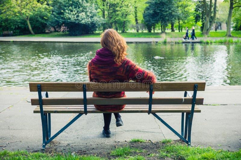 Vrouw sittng op bank door een vijver in het park royalty-vrije stock foto's