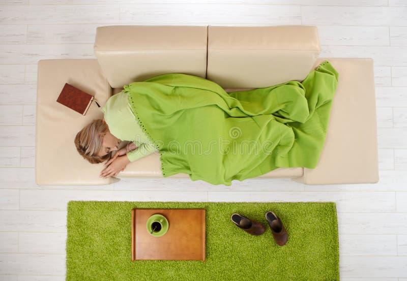 Vrouw slapend op laag thuis royalty-vrije stock afbeeldingen
