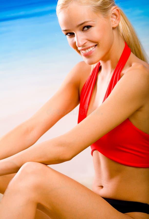 Vrouw in sport-slijtage op strand stock foto