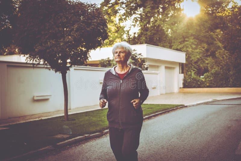 Vrouw in sporten die jogging in stadspark kleden stock foto