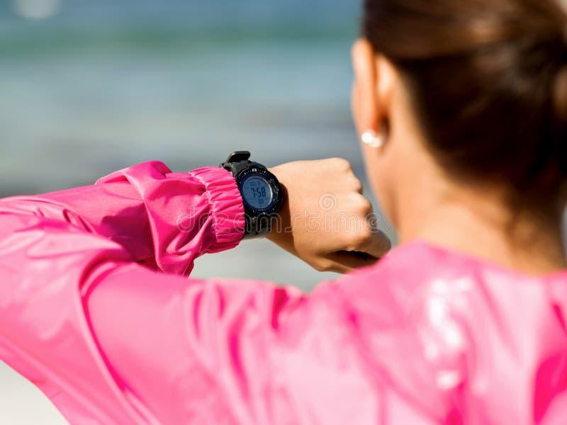 Vrouw in sportkleding die smartwatch gebruiken stock fotografie