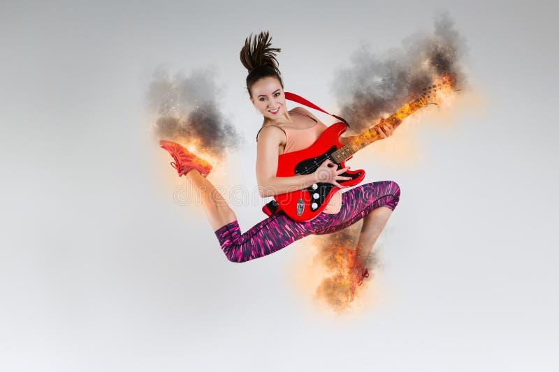 Vrouw in sprong met een brandende gitaar royalty-vrije stock foto
