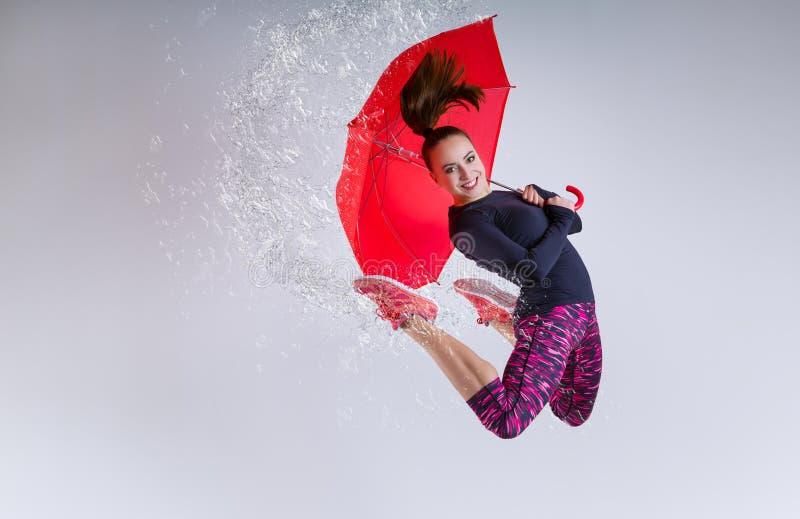 Vrouw in sprong met een paraplu royalty-vrije stock fotografie