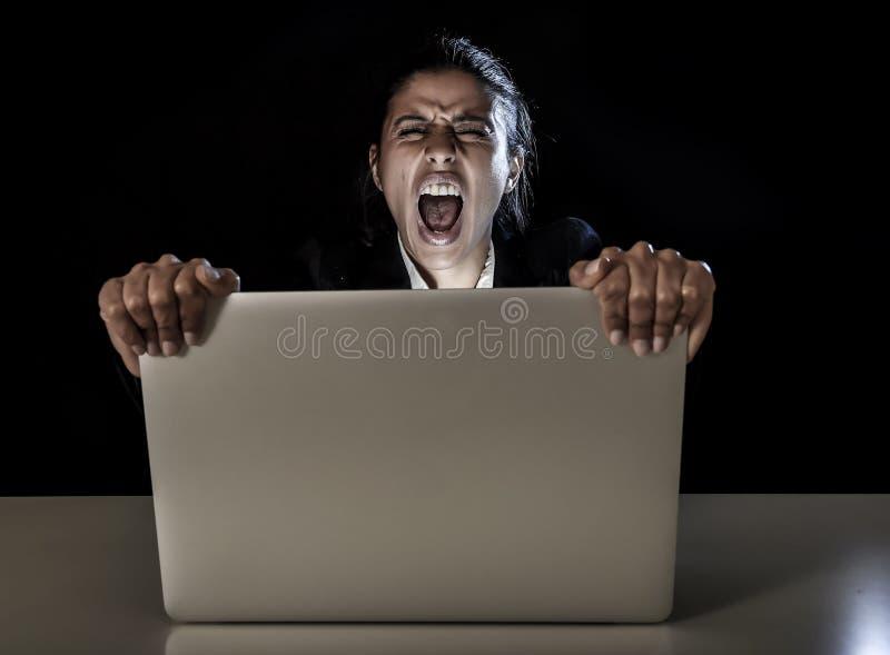 Vrouw of studentenmeisje die aan laptop computer laat bij nacht werken die het scherm het gillen houden stock foto